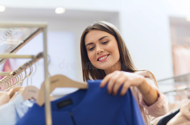 Szczęśliwy młodej kobiety wybierać odziewa w centrum handlowym fotografia royalty free