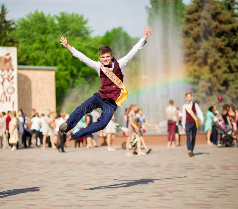Szczęśliwy młody absolwent z rękami w górę jest szczęśliwy kończyć roku szkolnego zdjęcia stock