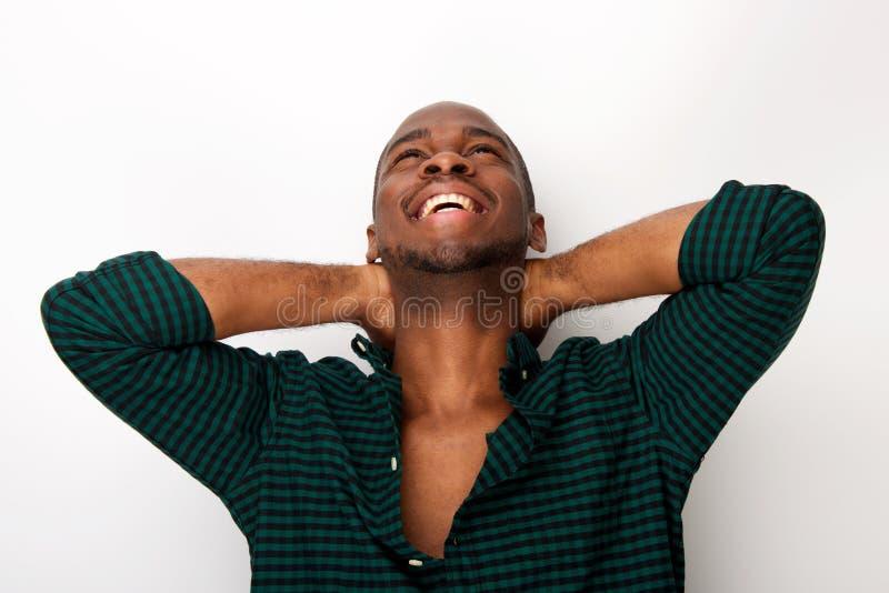 Szczęśliwy młody amerykanin afrykańskiego pochodzenia facet śmia się z rękami za głową przeciw odosobnionemu białemu tłu zdjęcie royalty free