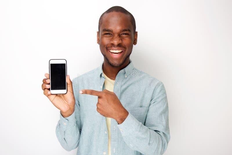 Szczęśliwy młody amerykanin afrykańskiego pochodzenia mężczyzny mienia telefon komórkowy i wskazywać ekranizować obrazy royalty free