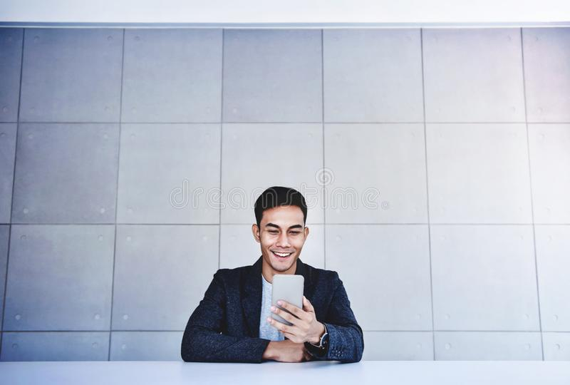 Szczęśliwy Młody Azjatycki biznesmen Pracuje na Smartphone Ono uśmiecha się i Siedzieć przy biurkiem w Przemysłowej Loft miejsce  obrazy royalty free