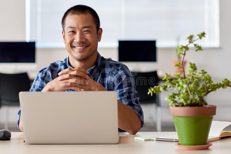 Szczęśliwy młody Azjatycki przedsiębiorca przy pracą w nowożytnym biurze zdjęcia stock