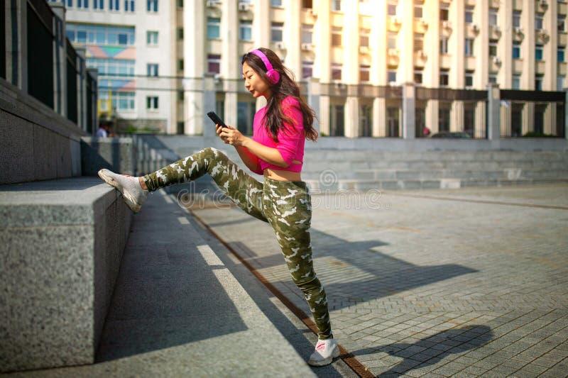 Szczęśliwy młody azjatykci kobiety szkolenie Jest s?uchaj?ca muzyka od s?uchawek i patrze? smartphone obraz royalty free