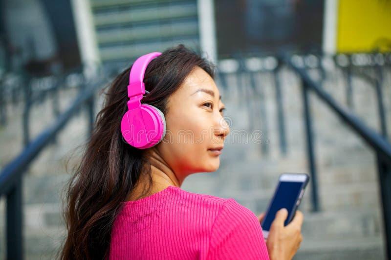Szczęśliwy młody azjatykci kobiety szkolenie Jest s?uchaj?ca muzyka od s?uchawek i patrze? smartphone zdjęcie royalty free