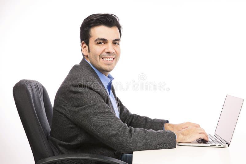 Szczęśliwy młody biznesmen pracuje na laptopie obraz royalty free