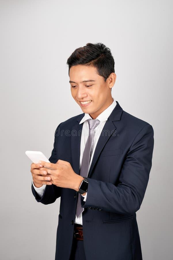 Szczęśliwy młody biznesmen texting jego kolega, przyjaciele, klienci fotografia stock