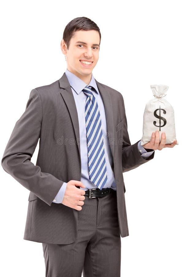Szczęśliwy młody biznesmen trzyma torbę z dolar amerykański znakiem fotografia stock