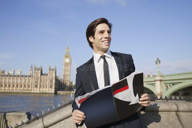 Szczęśliwy młody biznesmen z książkową pozycją przeciw Big Ben zegarowy wierza, Londyn, UK zdjęcie stock