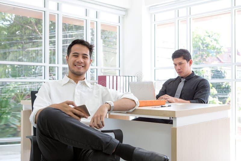Szczęśliwy młody biznesmena obsiadanie w biurze Biznes na Mobil obrazy royalty free