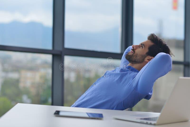 Szczęśliwy młody biznesowy mężczyzna przy biurem zdjęcia royalty free