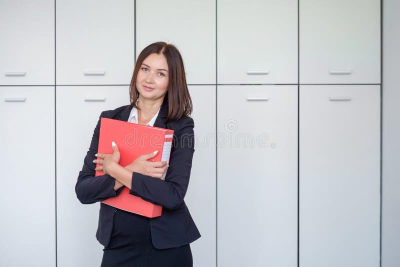 Szczęśliwy młody bizneswoman trzyma czerwonych ono uśmiecha się I segregatoru obrazy royalty free