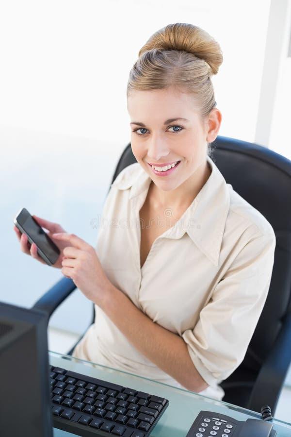 Szczęśliwy młody blondynka bizneswoman używa jej telefon komórkowego obrazy stock