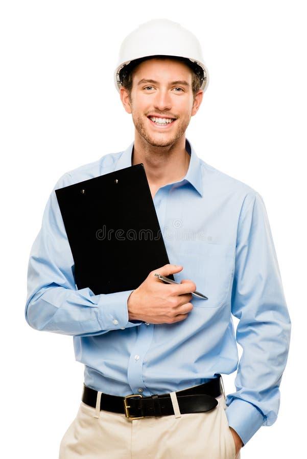 Szczęśliwy młody brygadier na placu budowy z ciężkiego kapeluszu bielu backgro obraz stock
