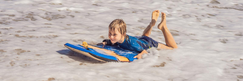 Szczęśliwy młody chłopak bawiący się na plaży na wakacjach, z Boogie Board BANNER, LONG FORMAT obraz royalty free