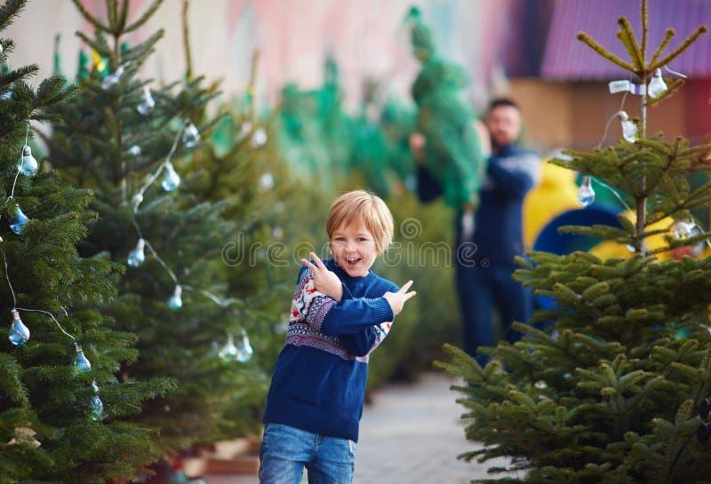 Szczęśliwy młody chłopak, dzieciak na targu choinkowym w zimowe święta zdjęcia royalty free