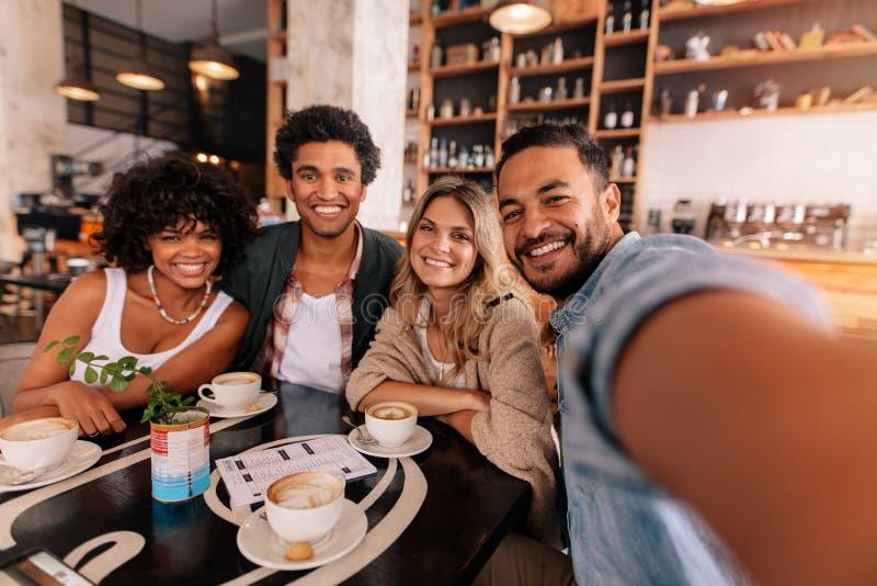 Szczęśliwy młody człowiek bierze selfie z przyjaciółmi w kawiarni zdjęcie royalty free