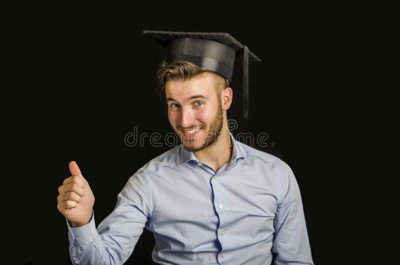 Szczęśliwy młody człowiek kończy studia, z kapeluszem fotografia stock