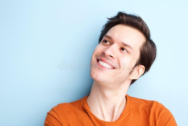 Szczęśliwy młody człowiek ono uśmiecha się przeciw błękitnemu tłu fotografia stock