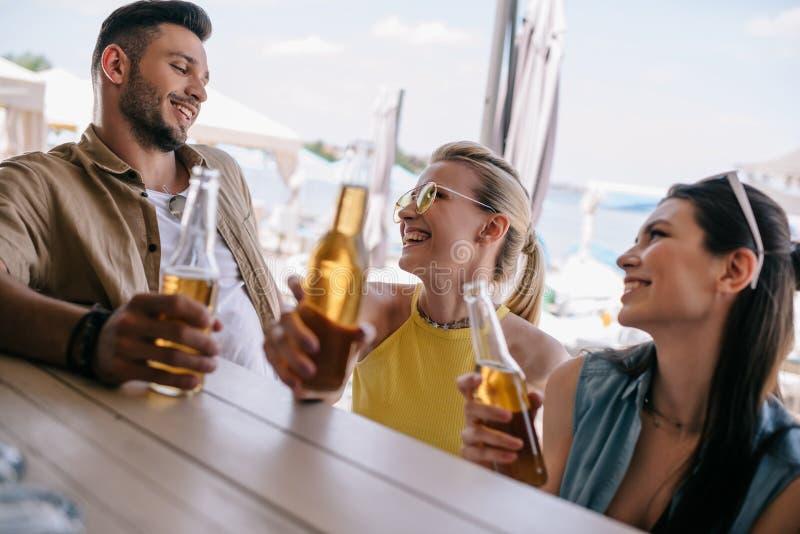 szczęśliwy młody człowiek patrzeje piękne uśmiechnięte dziewczyny i pije piwo wpólnie przy plaża barem obraz stock