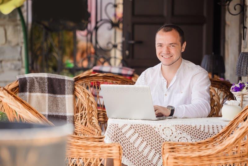 Szczęśliwy młody człowiek pracuje na laptopie outdoors obraz royalty free