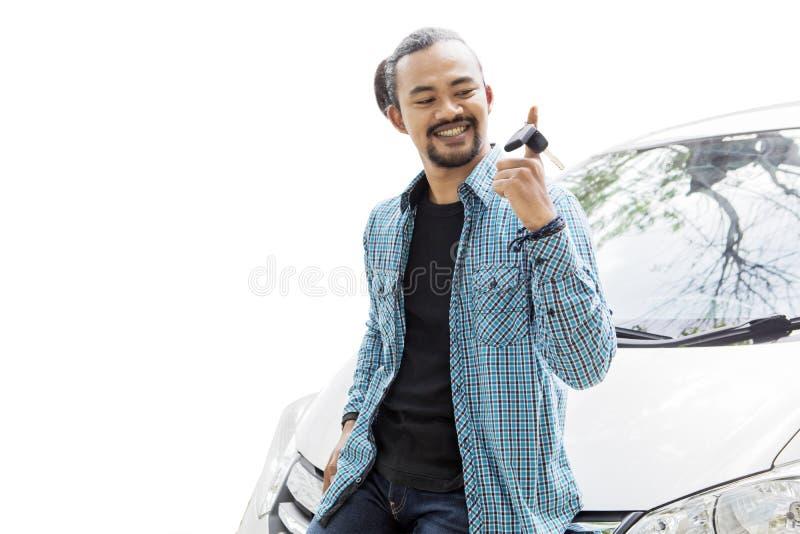 Szczęśliwy młody człowiek przekręca nowego samochodu klucz na studiu obraz royalty free