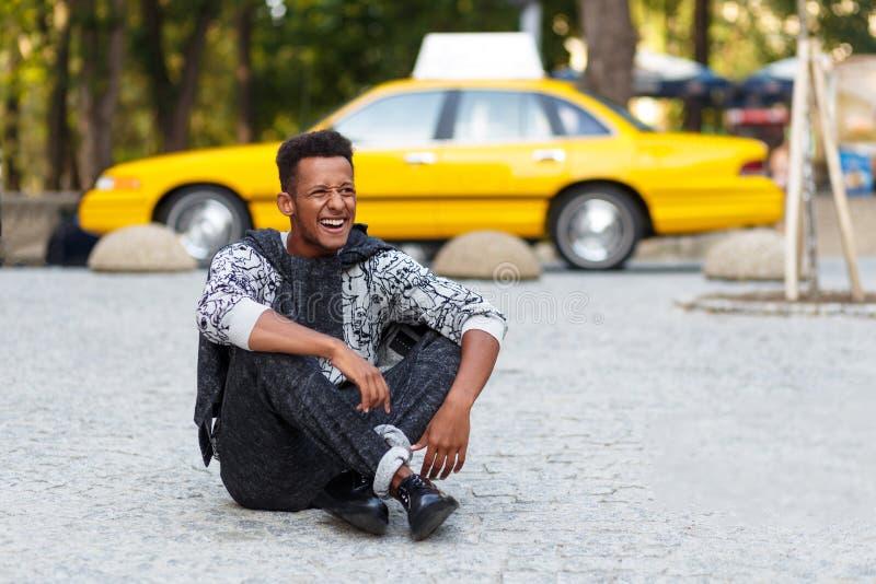 Szczęśliwy młody człowiek sadzający modnisia puszek na bruk drodze z krzyżować nogami, odosobnionymi na żółtym zamazanym taxi tle obraz stock