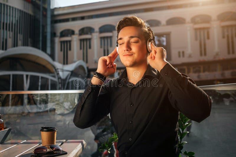 Szczęśliwy młody człowiek siedzi przy talbe outside i słucha muzyka przez hełmofonów On enjoyes ja Faceta chwyta ręki na hełmofon zdjęcie royalty free