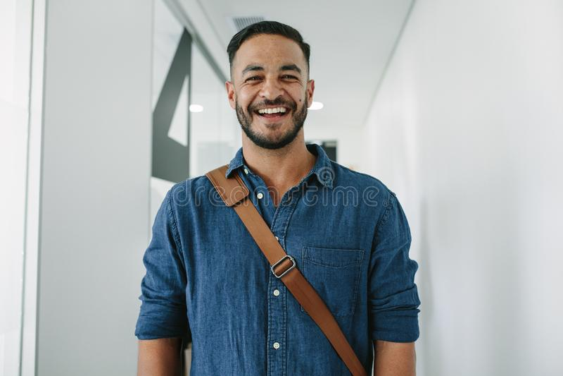 Szczęśliwy młody człowiek w biurowym korytarzu zdjęcia royalty free