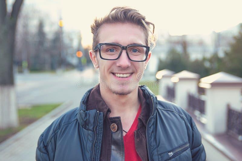 Szczęśliwy młody człowiek wewnątrz outwear na ulicie fotografia royalty free