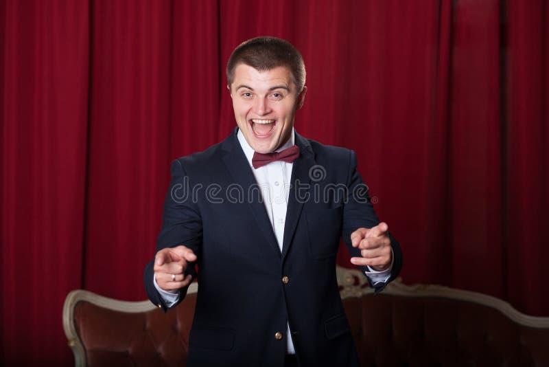 Szczęśliwy młody człowiek wyraża positivity w kurtce i bowtie zdjęcie royalty free