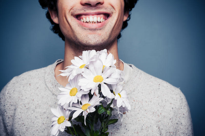 Szczęśliwy młody człowiek z kwiatami fotografia royalty free