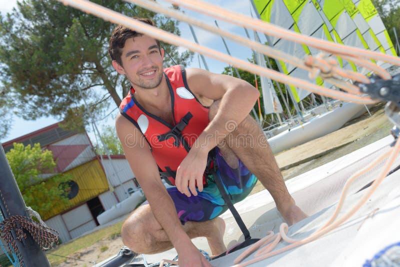 Szczęśliwy młody człowiek z ochrony kamizelką wokoło żeglować obrazy royalty free