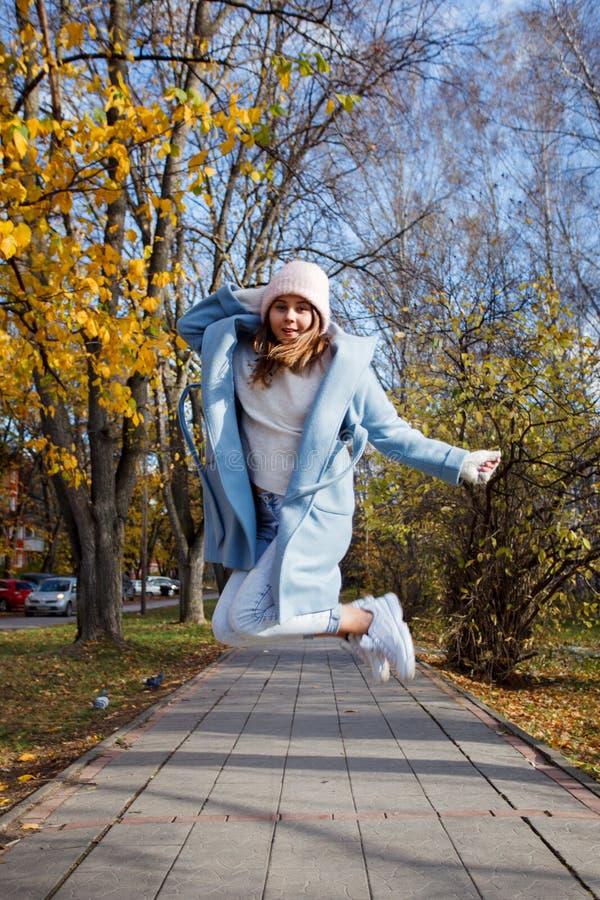 Szczęśliwy młody dorosłej kobiety odprowadzenie przy pięknego jesieni miasta ulicznym jest ubranym ciepłym kapeluszem obraz royalty free