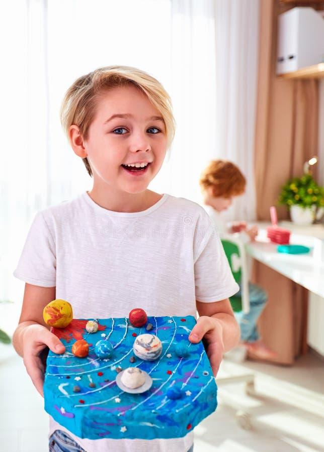 Szczęśliwy młody dzieciak, chłopak pokazujący model układu słonecznego zrobiony z plastycyny, pokój dla dzieci tło fotografia royalty free