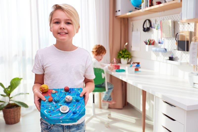 Szczęśliwy młody dzieciak, chłopak pokazujący model układu słonecznego zrobiony z plastycyny, pokój dla dzieci tło zdjęcie royalty free