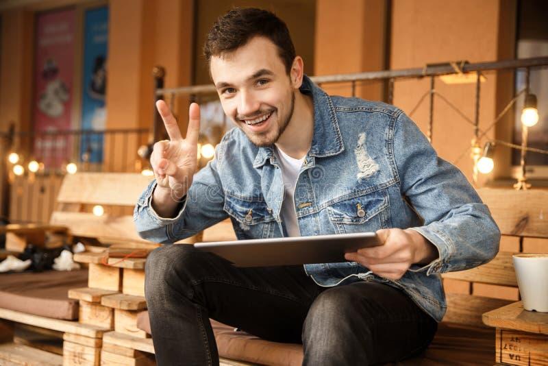Szczęśliwy młody facet jest przyglądający kamera i pokazywać zwycięstwo gest z jego prawą ręką podczas gdy trzymający jego pastyl zdjęcia stock