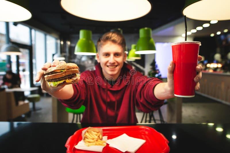 Szczęśliwy młody facet trzyma hamburger i pije w jego rękach, pokazuje kamerę Ostrość na hamburgeru i czerwień napoju szkle zdjęcie stock
