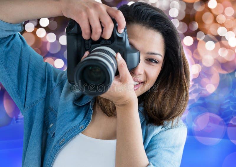 szczęśliwy młody fotograf bierze fotografię Brown, błękitnego i białego bokeh tło, obraz stock