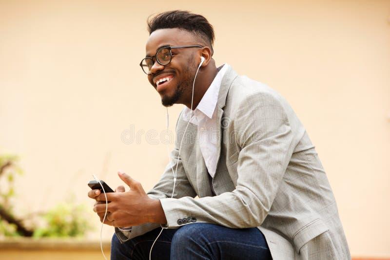 Szczęśliwy młody murzyna obsiadanie na zewnątrz słuchania muzyka z słuchawkami obrazy stock