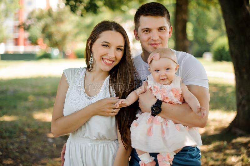 Szczęśliwy młody ojciec i matka odprowadzenie z śliczną dziewczynką w normie zdjęcia royalty free