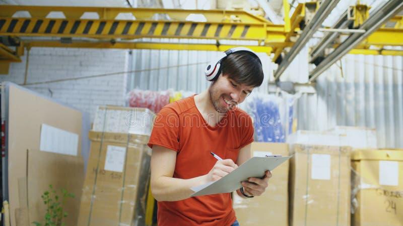 Szczęśliwy młody pracownik w przemysłowym magazynowym słuchaniu muzyka i tanu podczas pracy Mężczyzna w hełmofonach zabawę przy zdjęcia royalty free