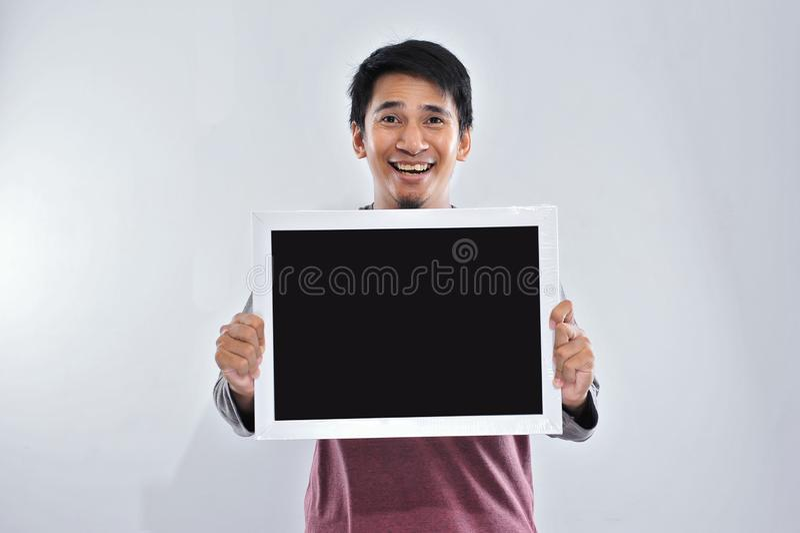 Szczęśliwy młody przystojny azjatykci mężczyzny mienie i seansu pusty blackboard gotowi dla twój teksta deska lub zdjęcie stock