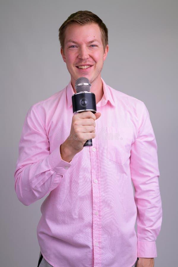 Szczęśliwy młody przystojny biznesmen jak gospodarza z mikrofonem obraz stock