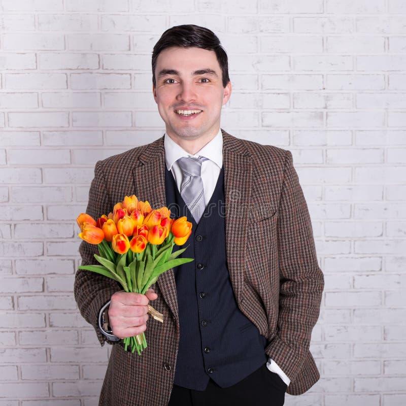 Szczęśliwy młody przystojny mężczyzna z kwiatami nad biel ścianą zdjęcia stock