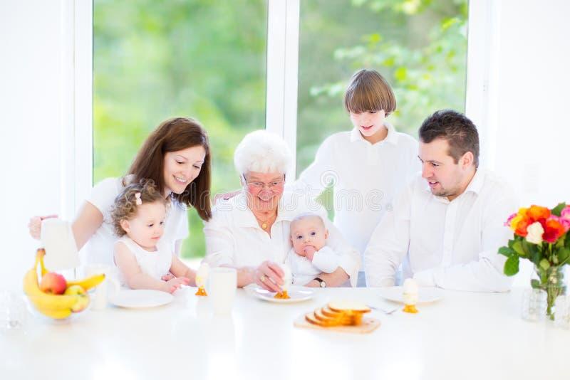 Szczęśliwy młody rodzinny cieszy się Wielkanocny śniadanie zdjęcie royalty free