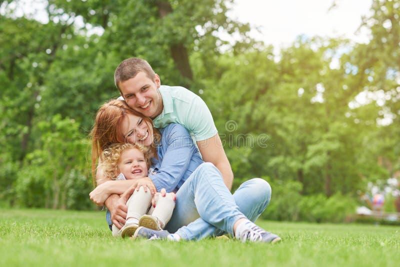 Szczęśliwy młody rodzinny relaksować przy parkiem fotografia royalty free