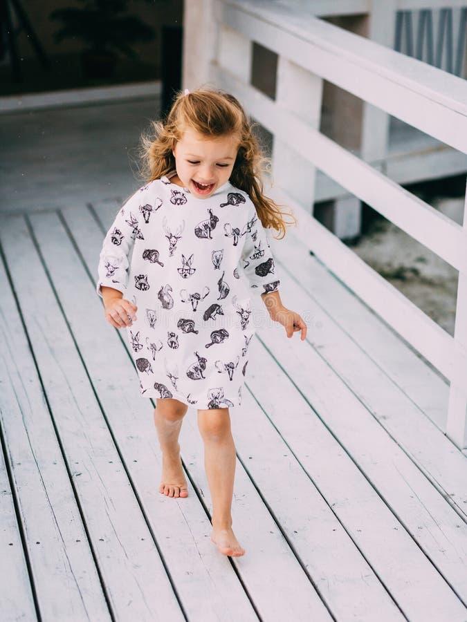Szczęśliwy mała dziewczynka bieg na plaży fotografia royalty free