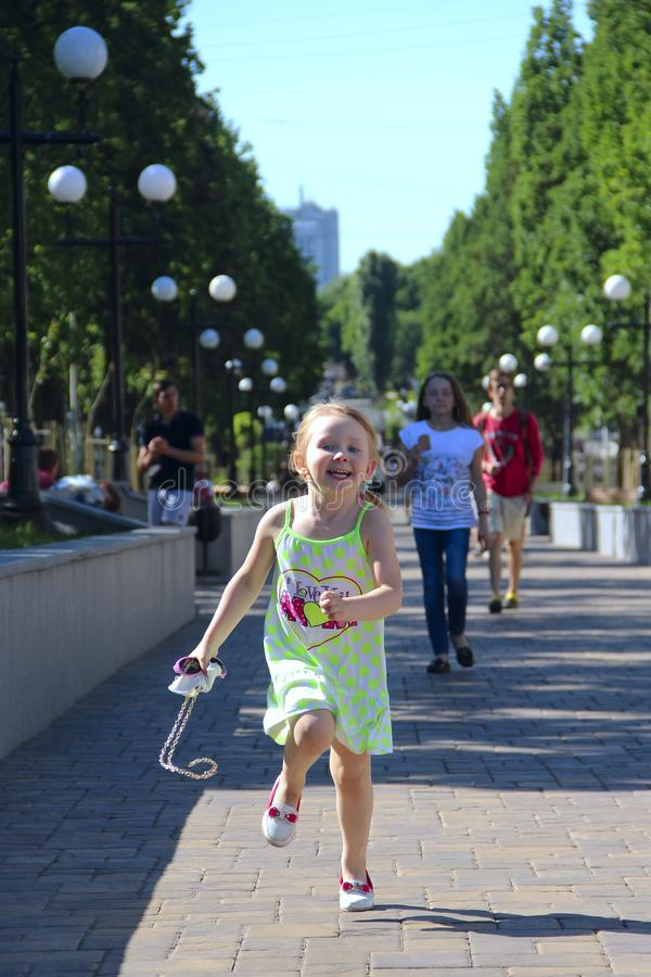Szczęśliwy mała dziewczynka bieg w miasto parku Pozytywni dziecięcy emitions obraz royalty free