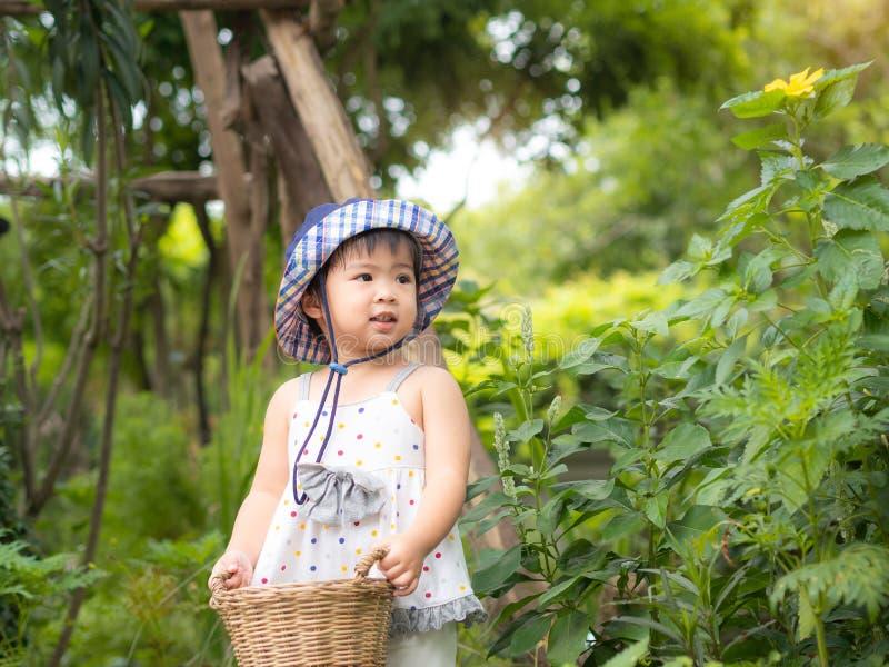 Szczęśliwy mała dziewczynka chwyt kosz w gospodarstwie rolnym Uprawiać ziemię & Childre obrazy royalty free