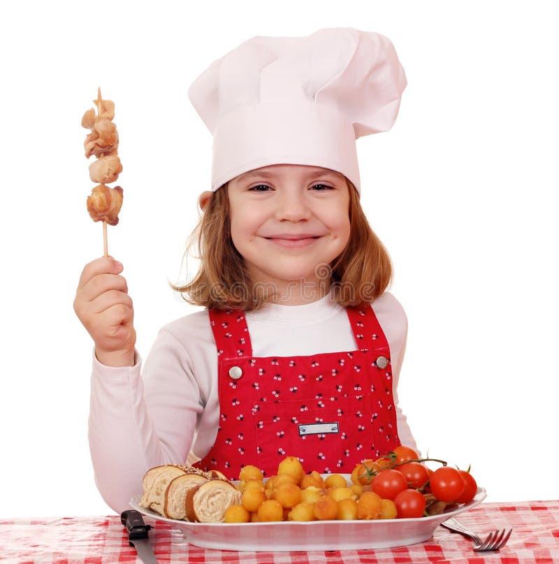 Mała dziewczynka kucharz z piec na grillu kurczaka mięsem fotografia royalty free